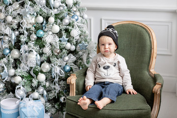 Portrait little boy. Happy new year. decorated Christmas tree. Christmas morning in bright living room. Standing on a green chair