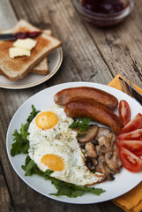 English breakfast. Eggs, sausages, mushrooms, tomatoes, toast bread. Eating tasy food over rustic wooden table.