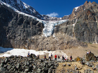 Hikers contemplating the amazing glacier of Mount Edith Cavell mountain at  Jasper National Park, Alberta, Canada