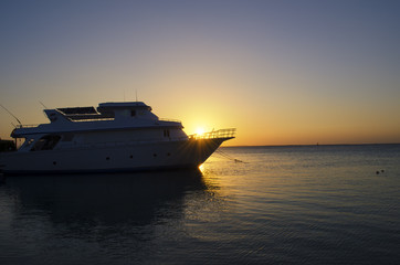 sunset over the sea with a yacht