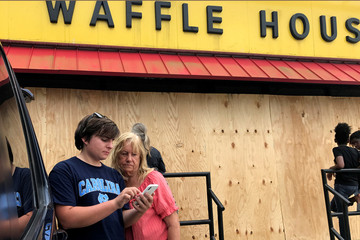 A youth checks weather data on his phone as he waits to eat at a Waffle House before Hurricane Florence comes ashore on Wilmington