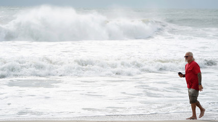 A man takes photos of the surf before Hurricane Florence comes ashore on Carolina Beach