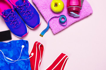Ultra violet female sneakers, pink top blue sporting leggings and water bottle on pastel pink background flat lay top view with copy space. Sports shoes, fitness, concept of healthy lifestile.