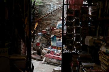 """Unusable old books are piled up outside the """"Acqua Alta"""" bookstore in Venice"""