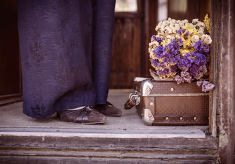 Suitcase, dried flowers and  fragment of female legs 2