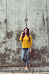 Casual beauty. Full length of beautiful young woman looking at camera with smile while standing against concrete background outdoors