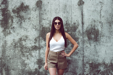 Sexy and stylish. Beautiful young woman looking at camera while standing against concrete background outdoors