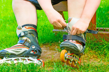 The skater binds the roller skates on the bench. Closeup inline skates in the green grass. In-line skating. Tackling laces on roller skates