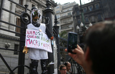 A demonstrator takes a picture of a puppet hanging from a fence of the National Congress during a national teachers strike, in Buenos Aires