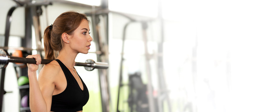 Athletic workout advertisement banner - cute girl has a hard  in the gym, doing exercises with barbells.