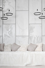 Many pillows lie on the couch, which is covered with a large plush veil against the background of a marble wall