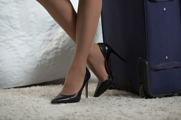 Woman feet in black high heel shoes. Standing at big suitcase. Busines trip concept.