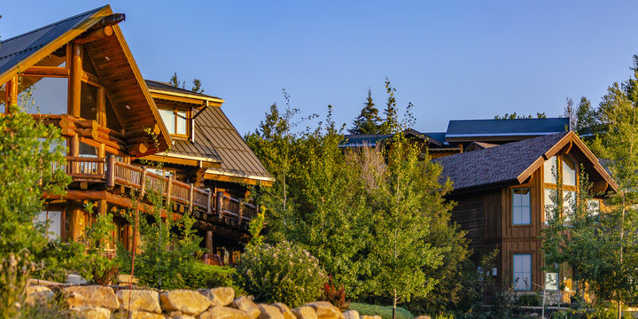 Two cabins in luxury neighborhood at sunset pano