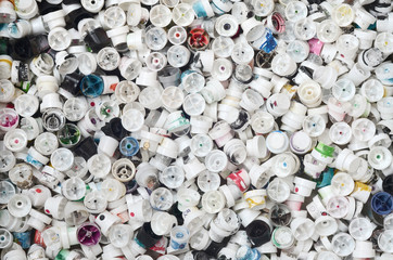 A large number of caps from cans of aerosol paint for graffiti. Smeared with colored paint nozzles lie in a huge pile