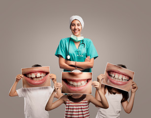 dentist doctor with children holding a picture of a mouth smiling