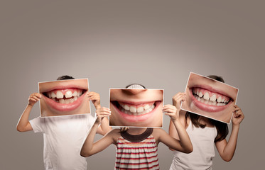 three children holding a picture of a mouth smiling