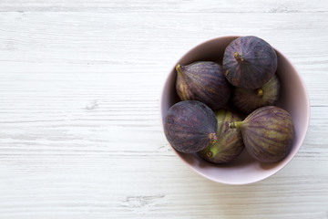 Fresh figs in a pink bowl on a white wooden background. Top view, overhead, from above. Space for text.
