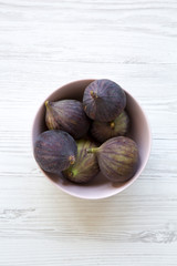 Fresh figs in a pink bowl on a white wooden background. Top view, overhead, from above. Close-up.
