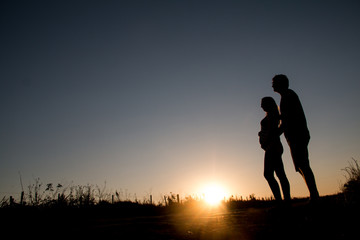 Young couple expects the first son looking into his eyes at sunset.