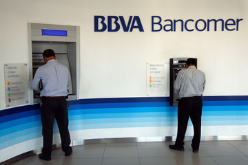 Customers draw money from an ATM at a BBVA Bancomer bank branch in Ciudad Juarez