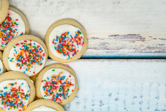 Vanilla white frosted homemade sugar cookies piled on a blue wooden background. Birthday rainbow sprinkles on the treats