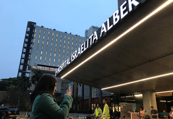 A woman takes a picture of the Albert Einstein hospital, where the Presidential candidate Jair Bolsonaro is hospitalized in Sao Paulo