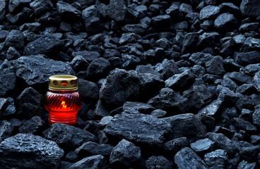 Vigil light, candle on cheap of coal