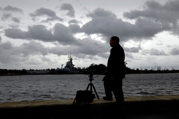 Storm clouds pass over decommissioned battleship as a photographer takes pictures on the banks of the Cape Fear River before the arrival of Hurricane Florence in Wilmington
