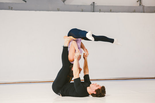 A young Caucasian male and female couple practicing acrobatic yoga in a white gym on mats. They are in the STAR pose.