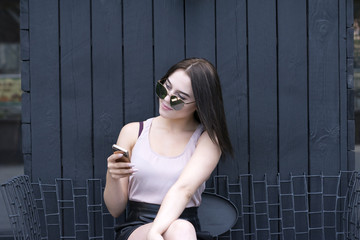 Outdoors picture of beautiful model texting using mobile phone