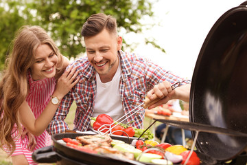 Young couple having barbecue with modern grill outdoors