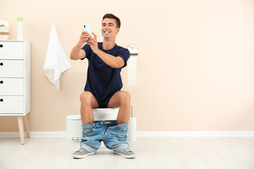 Young man taking selfie while sitting on toilet bowl at home