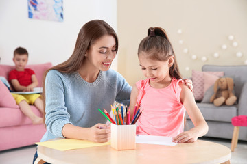 Cute little child drawing at table with young woman in playing room