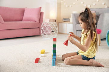 Cute little child playing with building blocks on floor, indoors