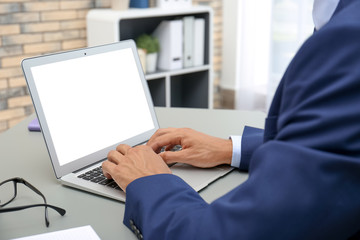 Man in office wear using laptop at table indoors