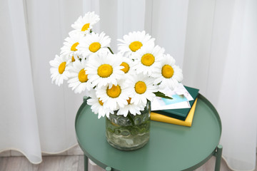 Vase with beautiful chamomile flowers on table