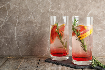 Glasses of fresh grapefruit cocktail with rosemary and space for text on color background