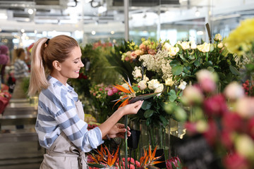 Beautiful female florist working in flower shop