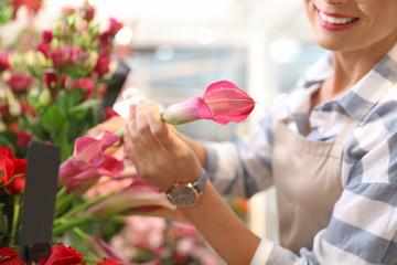 Female florist working in flower shop, closeup