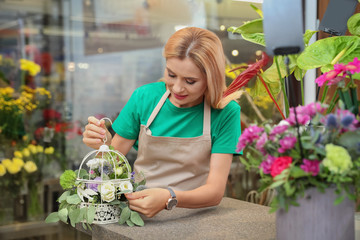 Female florist making beautiful composition in flower shop