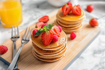 Tasty pancakes with berries on wooden board