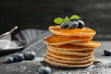 Tasty pancakes with berries and honey on slate plate