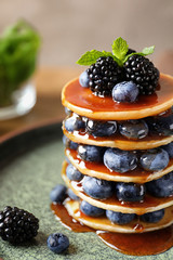 Tasty pancakes with berries and syrup on plate
