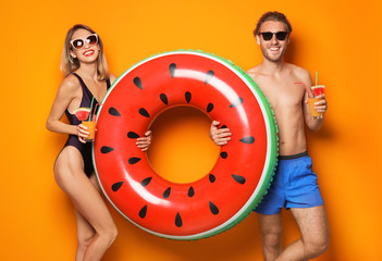 Happy young couple in beachwear with inflatable ring and cocktails on color background