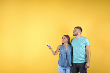 Young couple with air conditioner remote on color background, copy space text