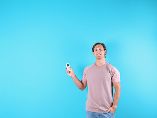 Young man with air conditioner remote on color background, copy space text