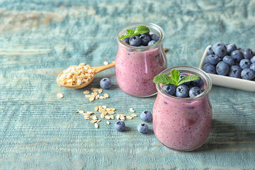 Tasty blueberry smoothie in jars, berries, oatmeal and space for text on wooden table