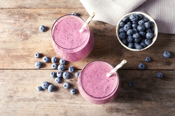 Flat lay composition with blueberry smoothie on wooden table