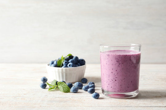 Tasty blueberry smoothie in glass, bowl with berries on table against light background with space for text