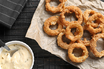 Cooling rack with homemade crunchy fried onion rings and sauce on wooden background, top view